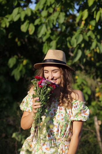 Smiling woman holding flowers while standing against trees