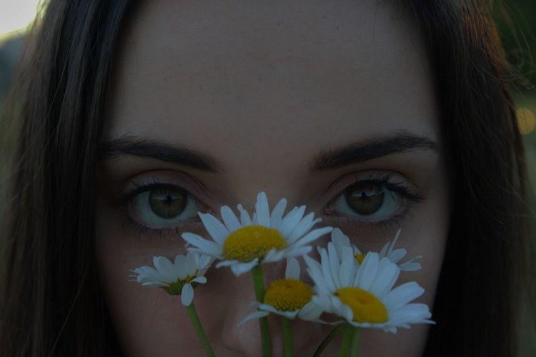 Close-up portrait of beautiful woman holding daises