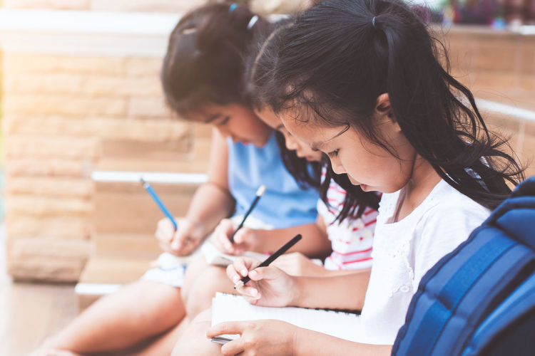 Girls studying while sitting on chair