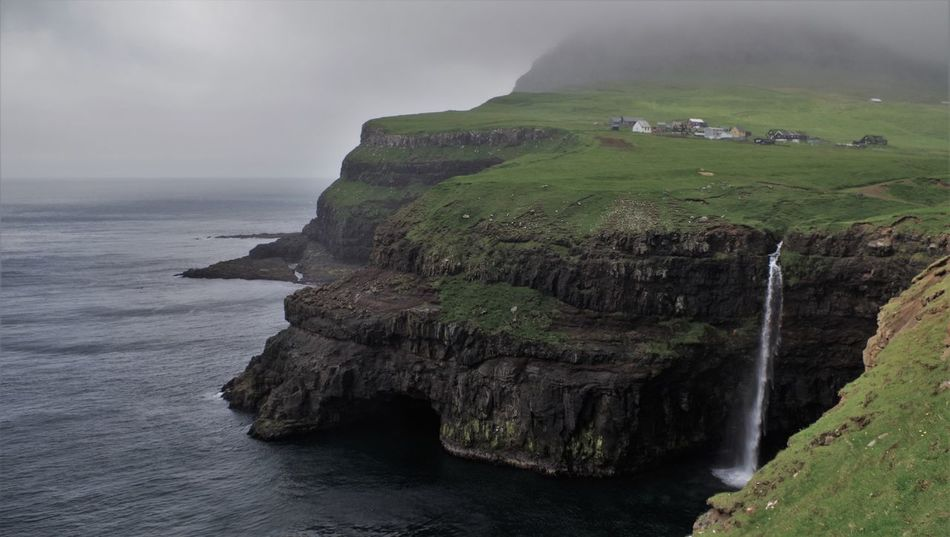 Famous gasadalur waterfall, the mountain peaks where in the fog when i was visiting. Cascade Coastline Day Downfall Epic Faroe Islands Faroes Gasadalur Houses Island Landscape Magnifique Mountains Nature No People Ocean Outdoors Rock - Object Scenics Sea Steep Storm Cloud Village Water Waterfall