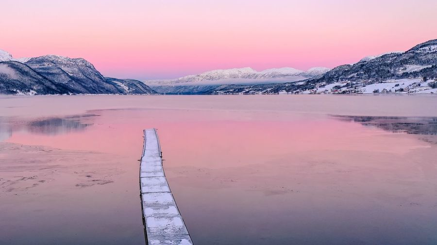 Scenic view of frozen lake against sky during sunrise