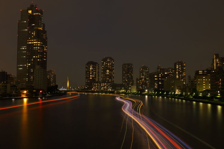 Light Trails On Sea Against Illuminated City At Night