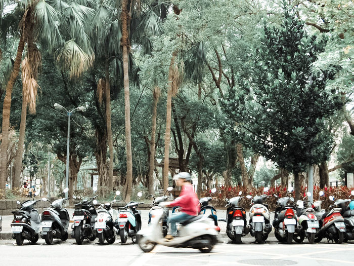 People riding motor scooter on road in city