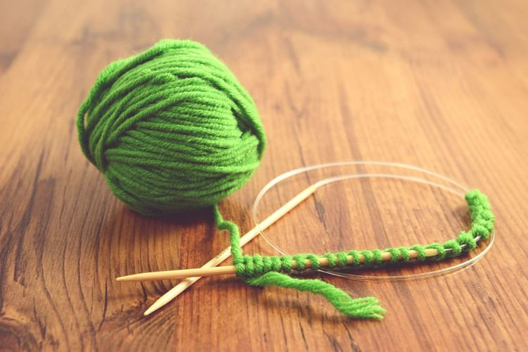 Knitting ball of wool with needle on wooden table