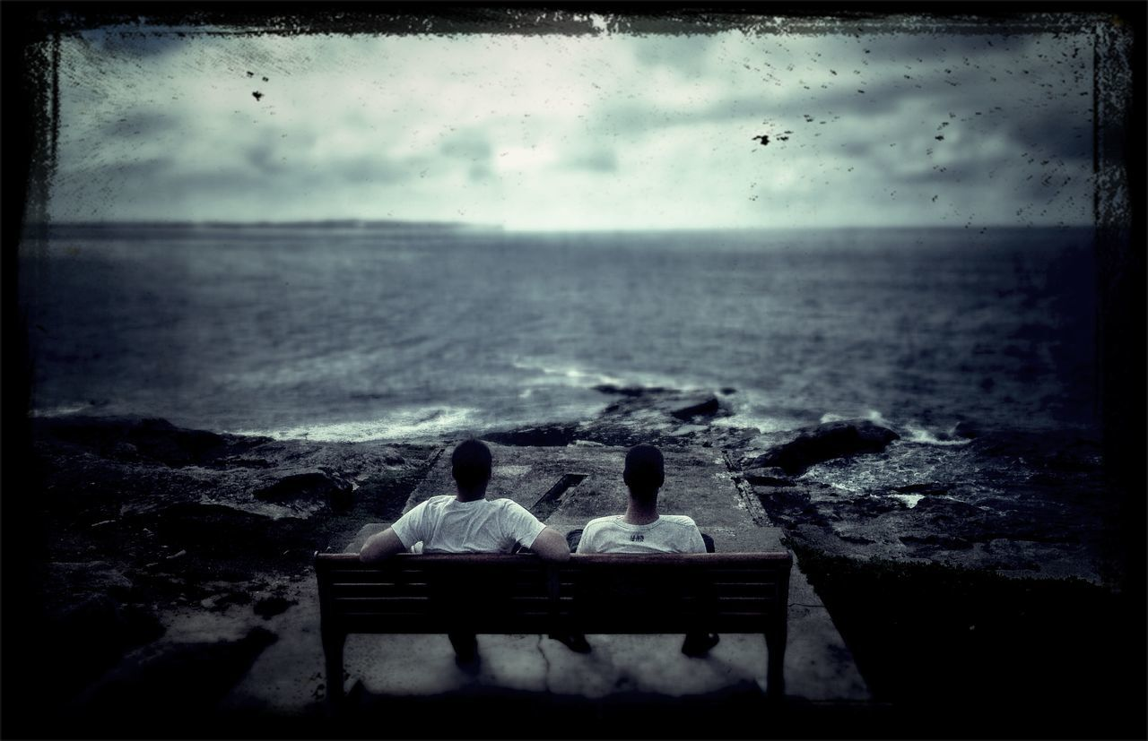 Rear view of two men sitting on bench overlooking sea