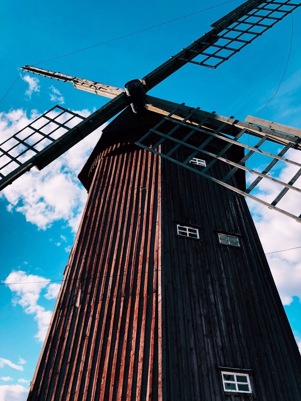 low angle view, architecture, built structure, sky, fuel and power generation, renewable energy, alternative energy, environmental conservation, cloud - sky, building exterior, nature, no people, day, wind turbine, turbine, wind power, building, traditional windmill, environment, outdoors, power supply