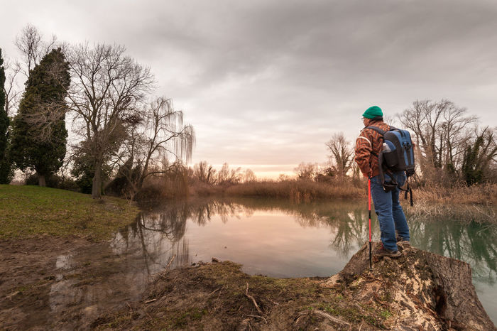 Hiker resting on river bank. Hike and people concept, travel,tourism. Active Backpack Beauty In Nature Casual Clothing Day Grass Hiker Lake Leisure Activity Lifestyles Men Nature One Person Outdoors Ramble Real People River Sky Standing Tree Water Wildlife