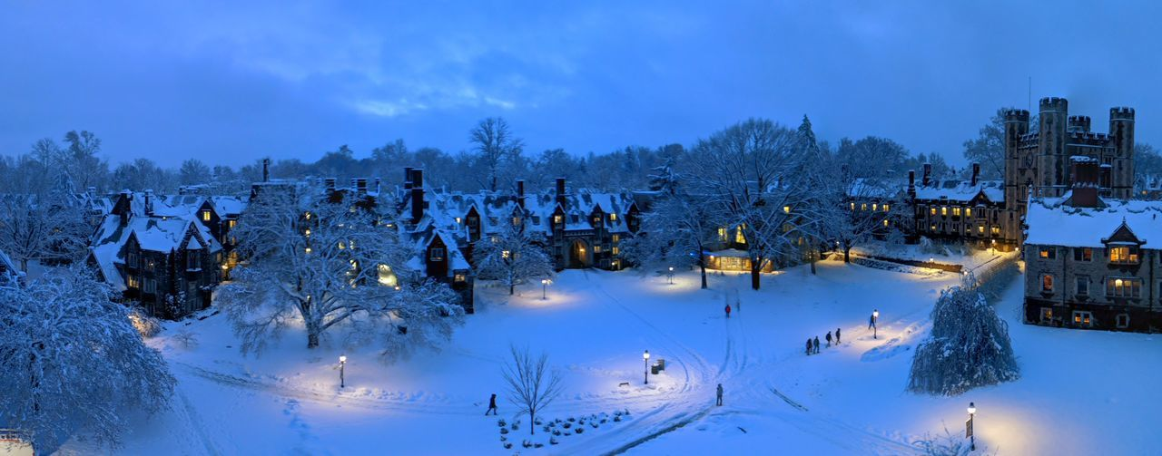 Panoramic view of snow covered field and houses against sky