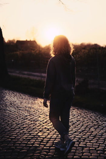 Rear view of woman walking on footpath at sunset