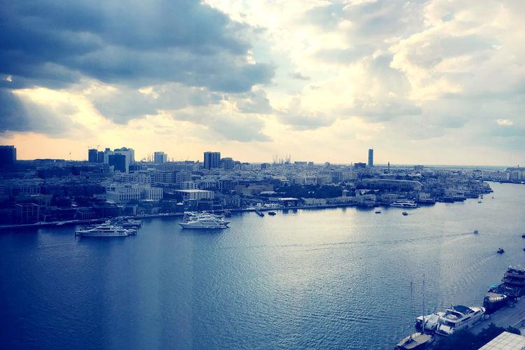 City buildings by sea against sky
