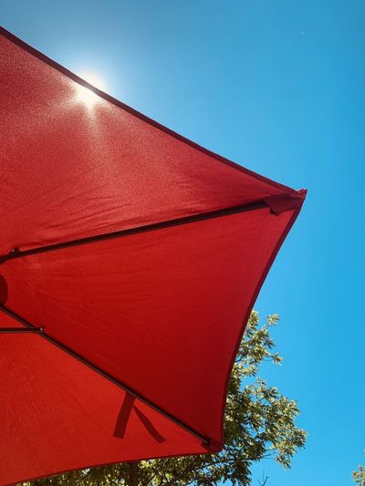 Low angle view of red umbrella against clear blue sky