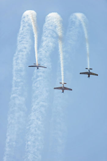 Low angle view of military airplanes performing airshow against sky