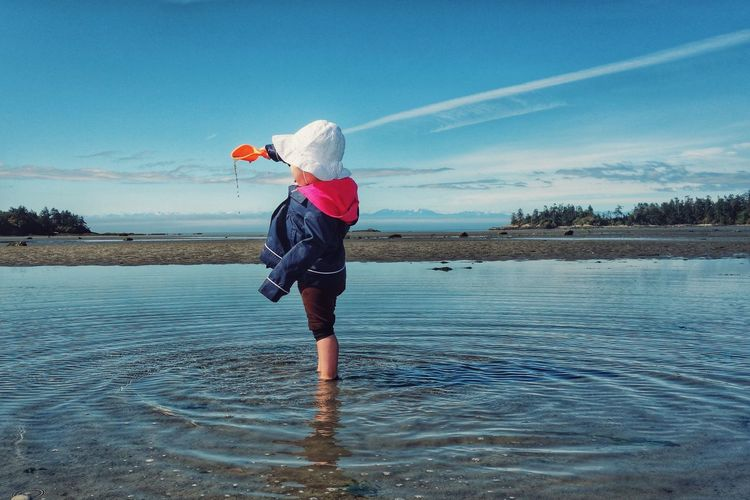 Day at the beach. Enjoying The Sun Beach Children Playing Rain Coat Standing Up Pouring Water Playing In The Water San Juan Islands Young Child Blue Sky Rippling Water Color Of Life Colour Of Life People And Places My Year My View Live For The Story The Great Outdoors - 2017 EyeEm Awards