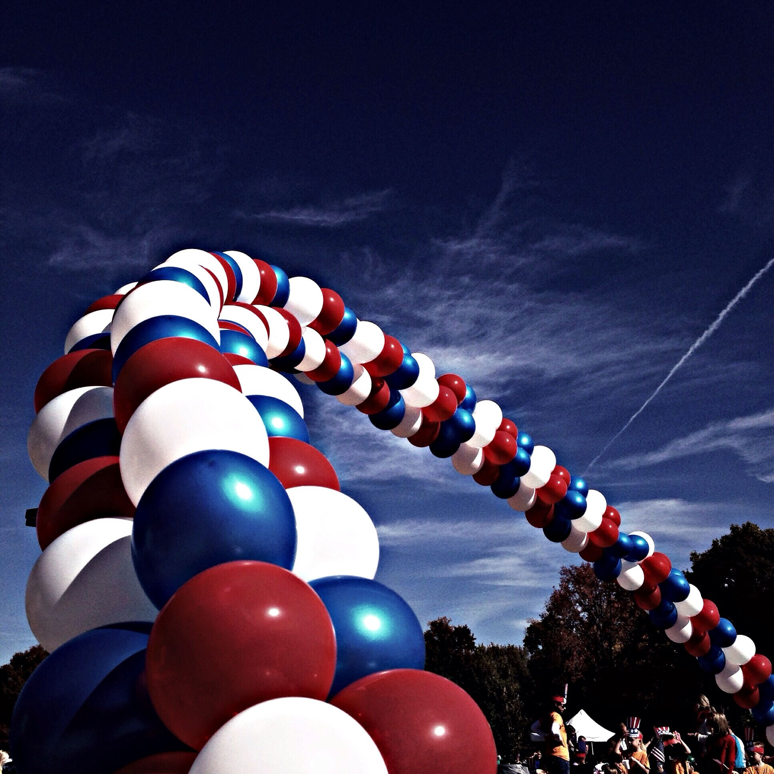 low angle view, sky, multi colored, blue, hot air balloon, cloud - sky, celebration, outdoors, no people, flag, red, decoration, day, balloon, hanging, arts culture and entertainment, flying, patriotism, cloud, in a row
