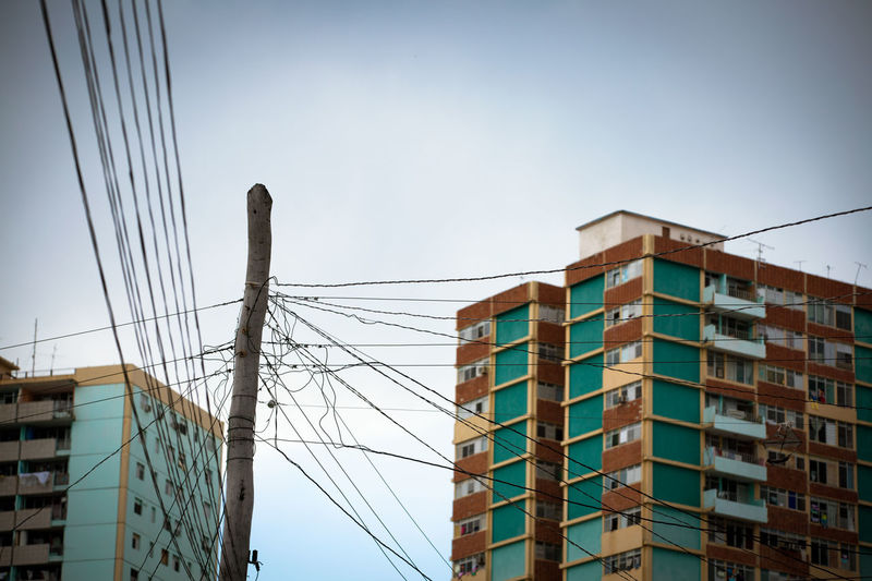 Architecture Building Building Exterior Built Structure Cable Chaos City City Life Day Development Energie High Section Low Angle View No People Old Outdoors Power Line  Residential Building Sky Strom Strommast Tall - High
