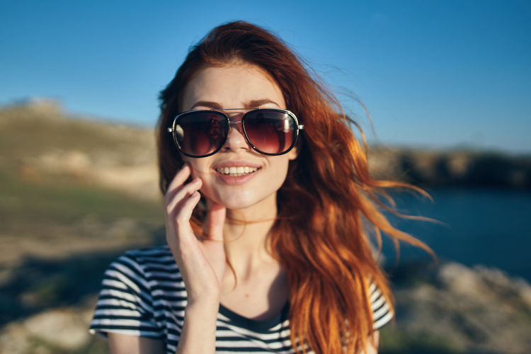 Portrait of smiling young woman wearing sunglasses against sky