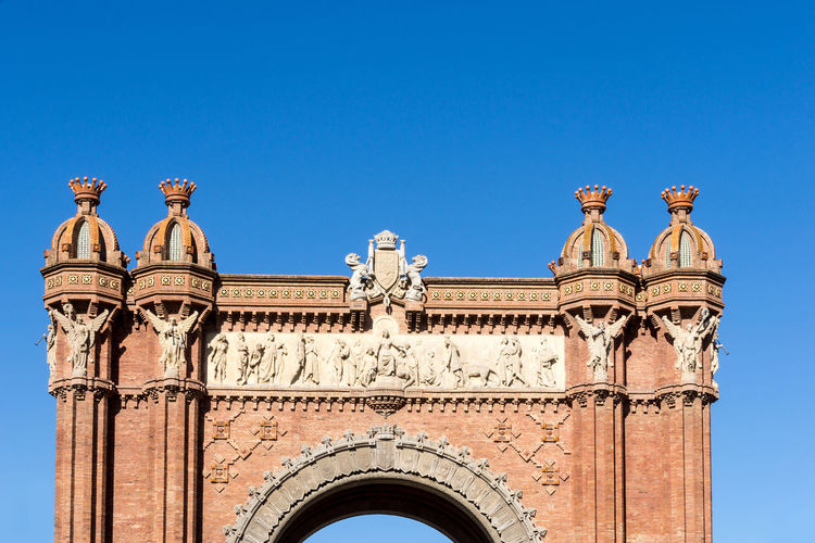 Low angle view of arc de triomf against clear blue sky