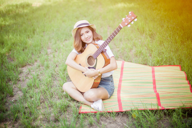 Young woman with guitar on grassy field at park