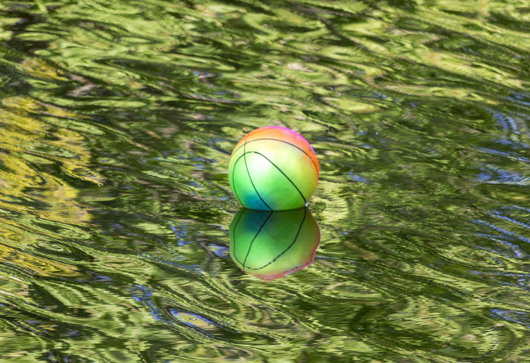 Reflection Ball Floating Floating On Water Green Color High Angle View Rippled Water