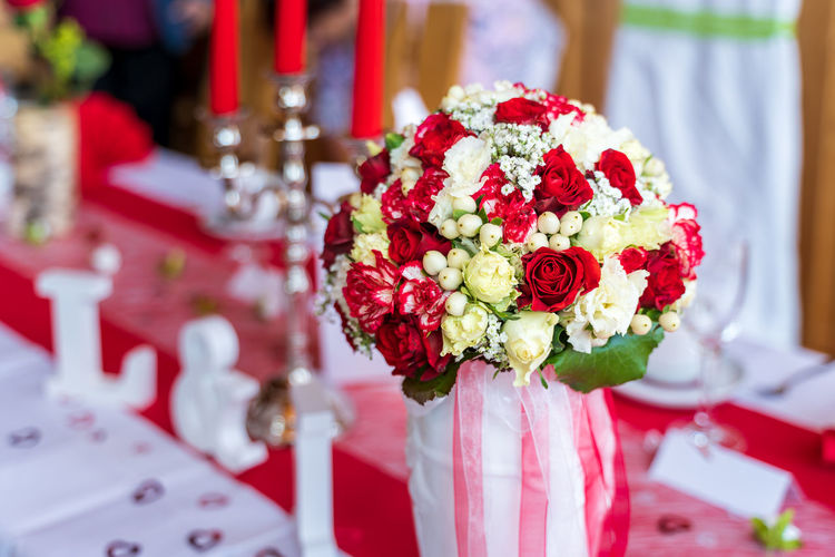 Red and white wedding bouquet at table - close up