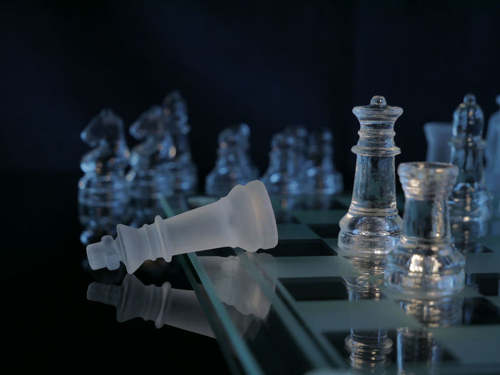 Close-up of chess pieces on board against blurred background