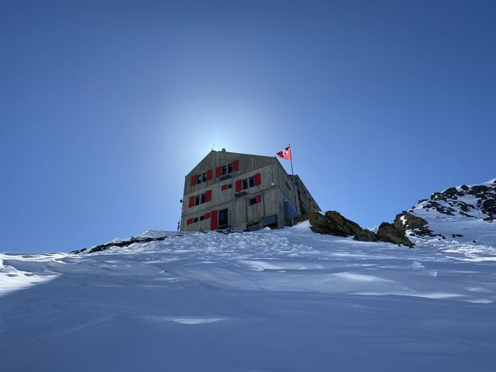 Built structure on snow covered mountain against clear blue sky