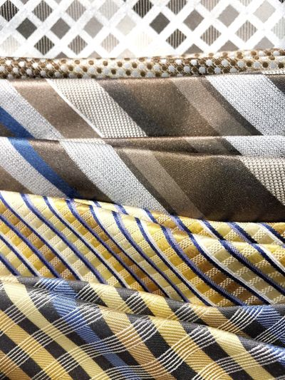 Man's tie colorful pattern background variety many dress clothes formal business attire accessory yellow beige
