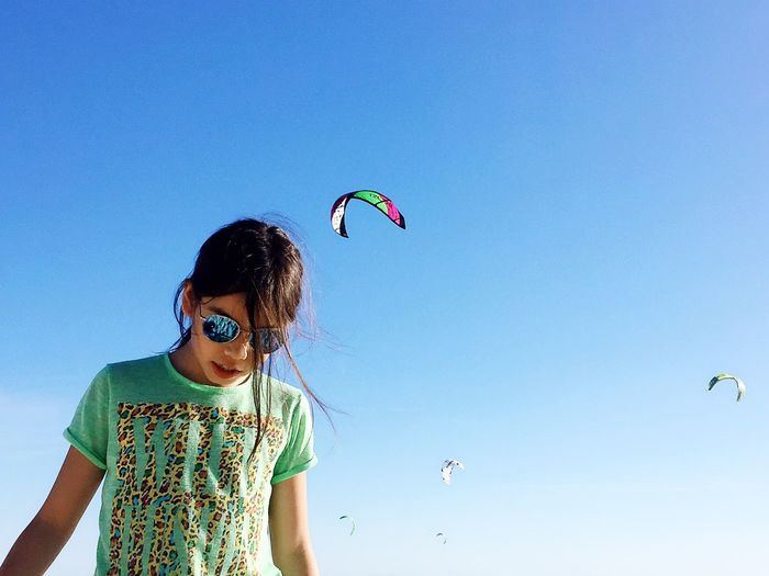 Low angle view of girl against clear sky with parachutes