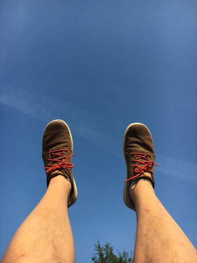Cropped legs of man against blue sky