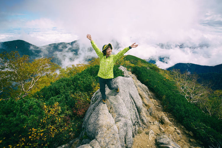 Woman with arms raised standing on mountains against sky