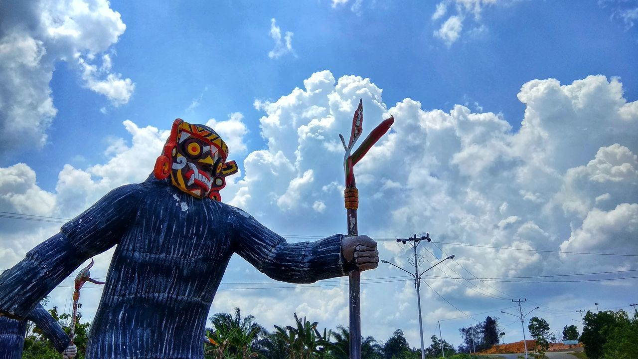 cloud - sky, sky, representation, human representation, art and craft, day, nature, sculpture, statue, one person, creativity, male likeness, low angle view, real people, tree, scarecrow, front view, outdoors, sunlight
