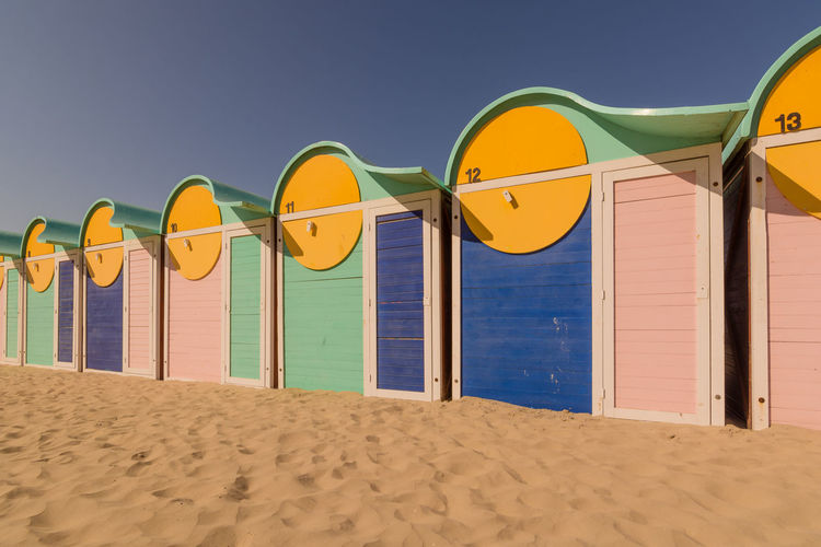 The end of summer. Beach Cabins Beach Life Beachphotography Blue Clear Sky Colorful End Of Summer Façade Fine Sandy Coast Shore Green Color In A Row Multi Colored No People Repetition Sea Sunset Light TakeoverContrast Tranquil Scene Vacations Vibrant Color Yellow Yellow Color