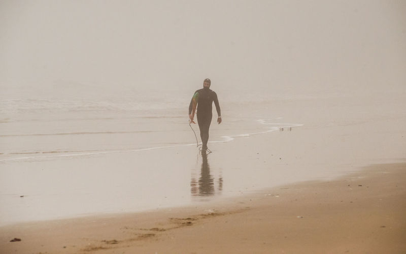 Surfer with surfboard walking on shore at beach