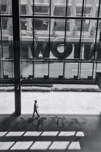 Man walking on street seen through glass window