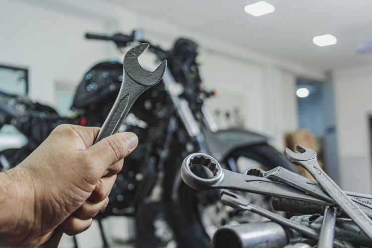 Cropped hand of mechanic holding wrench standing in garage