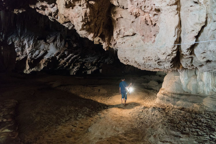 Rear view of man walking in cave