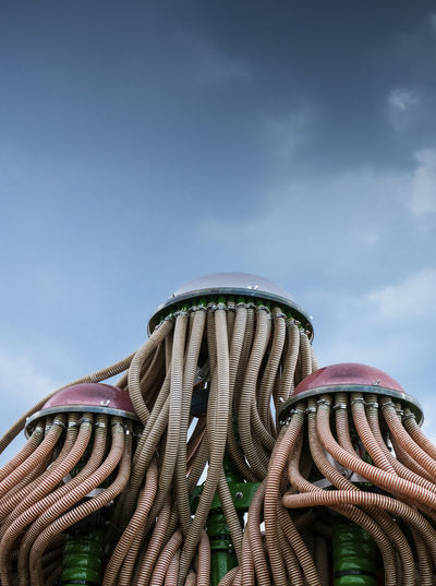 Sky Low Angle View Nature Cloud - Sky Day No People Metal Outdoors Copy Space Close-up Art And Craft Pattern Focus On Foreground Architecture Craft Sculpture Blue Creativity Built Structure Spiral Outdoor Play Equipment Trumpet Pipeline Pipe Alien Grain Conduit