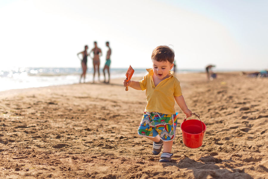 Toddler boy walking at the beach Beach Boys Carefree Casual Clothing Caucasian Ethnicity Childhood Enjoyment Escapism Full Length Fun Holding Innocence Leisure Activity Lifestyles Looking Down On The Move Person Random People Real People Sand Sand Bucket Toddler  Walking