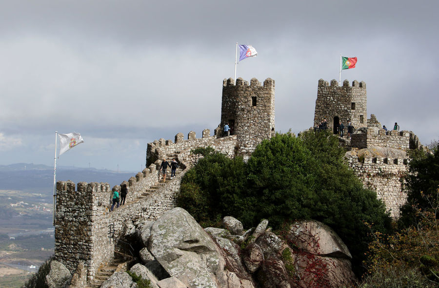 Visitors walk on top of the Castle of the Moors or Castelo dos Mouros in Sintra, Portugal. Moors Castle Portugal Sintra Sintra (Portugal) Sintra, Portugal Architecture Built Structure Castle Castle Of The Moors Cloud - Sky Day Flag Flags Fort Fortress History Nature No People Outdoors Patriotism Power In Nature Sky Stronghold Tower Travel Destinations