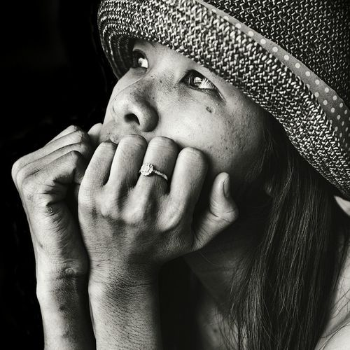 Close-up of sad woman looking away against black background