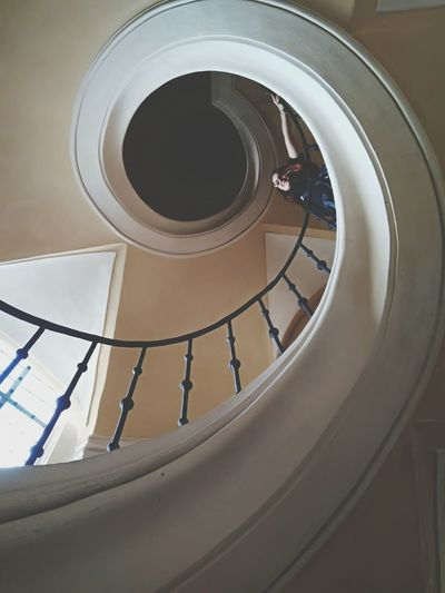 Low angle view of woman on spiral staircase at home