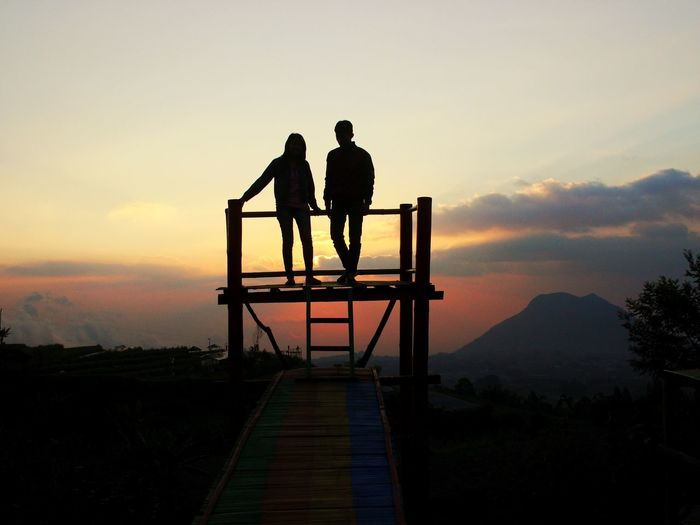 Silhouette couple standing on lookout tower against sky during sunset