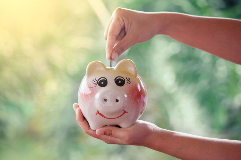 Woman hand putting coin into Piggy Bank Asian  Business Collecting Economy Kids Learning Piggy Bank Accounting Adorable Bank Child Coin Daughter Deposit Finance Fingers Fund Girl Hand Holding Money Pig Profit Saving Toy