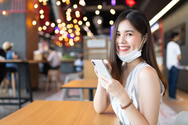 Portrait of smiling young woman holding mobile phone at table