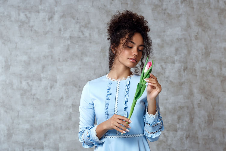 Beautiful woman holding tulip while standing against wall