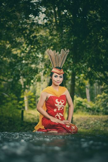 Young woman wearing traditional clothing sitting in forest