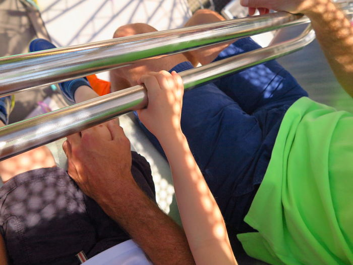 Low Section Of Father And Son Sitting On Amusement Park Ride