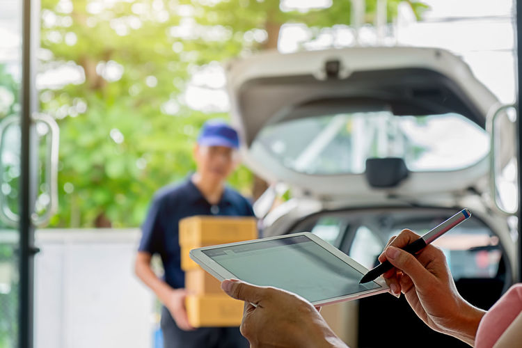 Cropped hands of woman signing on digital tablet with man holding boxes in car