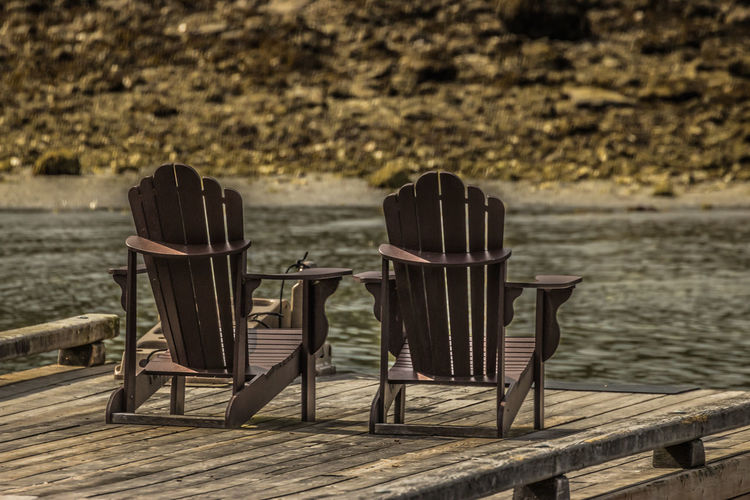 Empty chairs and table by lake