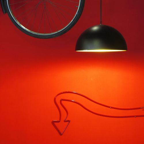 Close-Up Of Illuminated Lamp Against Red Background